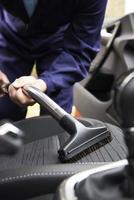 Mann saugt Sitz des Autos während der Autoreinigung foto