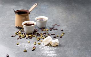 türkischer Kaffee mit Kaffeebohnen und Kardamom verstreut