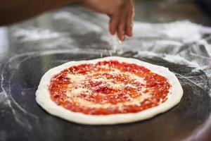 Käse auf hausgemachte Pizza streuen foto
