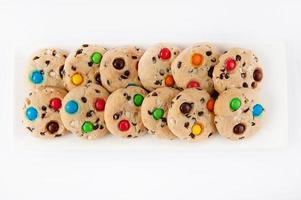 Kekse mit bunten Gummibärchen auf einem weißen rechteckigen Teller foto