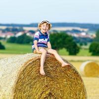 kleiner Junge, der im Sommer auf Heuballen sitzt