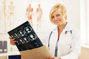junge Ärztin, die Umschlag mit Hirntomographie-Ergebnis öffnet