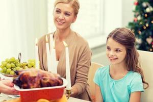 lächelnde Familie, die Feiertagsessen zu Hause hat foto