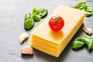 Lasagne Zutaten - trockene Blätter, Kirschtomate, Basilikum, Knoblauch, Käse