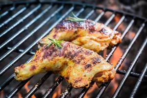 gebratene Hähnchenschenkel auf dem Grill mit Feuer