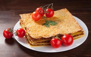Lasagne und Kirschtomaten auf einem Holzbrett foto