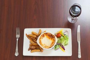 Hochwinkelansicht der Lasagne mit Kartoffeln und Salat foto