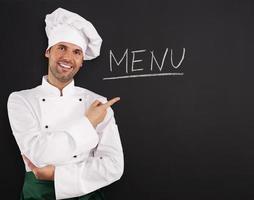 hübscher Koch zeigt Menü foto