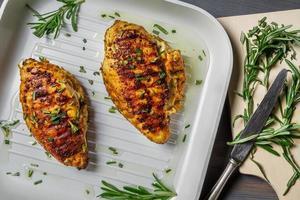 gebratene Hühnerbrust mit Rosmarin auf einer Pfanne foto