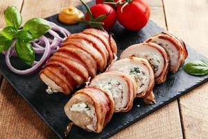 Mit Hühnerbrust gefüllter Feta-Käse und Kräuter im Speckmantel foto
