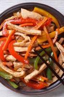 Huhn mit Gemüse Nahaufnahme auf einem Teller. Draufsicht vertikal