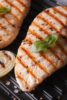 Hähnchenfilet mit Zwiebel auf einem Grillmakro. Vertikale