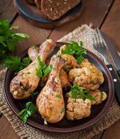 Hähnchenschenkel mit gebackenem Blumenkohl und Petersilie foto