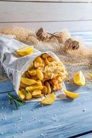heißer Fisch Kabeljau mit Pommes in Zeitung mit Zitrone foto