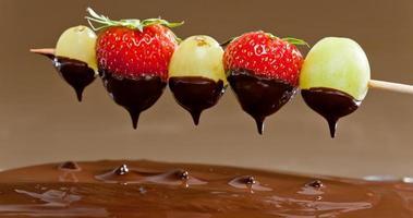 Obst wird in Schokoladenfondue getaucht foto