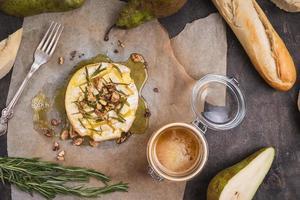 lecker gebackener Camembert mit Honig, Walnüssen, Kräutern und Birnen foto