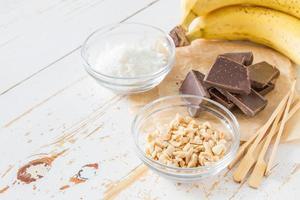 Bananen-Pops-Zubereitung - Banane, Schokolade, Nüsse, Kokosnusspulver, Sticks foto