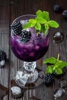 Brombeercocktail im Weinglas mit Minze und Eis foto