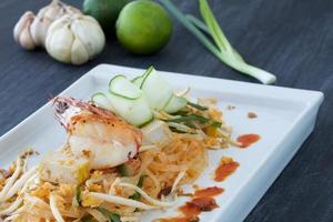 Pad Thai, Garnelen und Gemüse auf Teller mit Zutaten umgeben foto