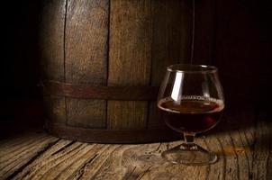 Gläser Brandy im Keller mit alten Fässern foto