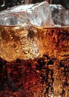 Blasen im Glas Cola mit Eis. foto