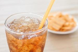 Glas Cola mit Snack auf weißem Teller foto