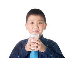 Junge trinkt Milch mit Milchschnurrbart, der Glas Milch hält foto