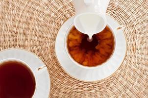 Milch fließt in eine Tasse Tee foto