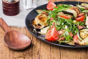 Auberginensalat mit Tomaten und Rucola foto