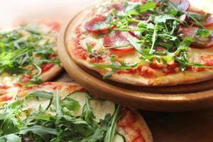 Pizza mit Wurst, Käse, Ruccola foto