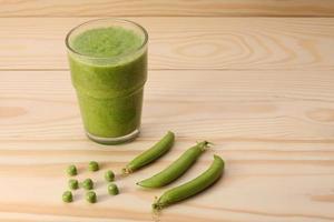 Smoothie mit grünen Erbsen in einem Glas und Erbsenschoten foto