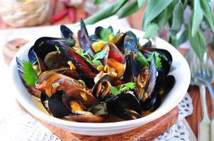 Suppe aus wilden Muscheln mit Weißwein, Gemüse, Salbei, Koriander foto