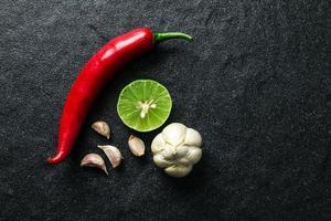 roter Chili, Knoblauch und Limettenzitrone auf schwarzem Stein anrichten foto