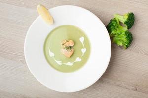 grünes Brokkoli-Cremesuppenpüree mit Lachsfilet und Zitrone foto