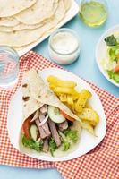 griechische Gyros mit Schweinefleisch, Gemüse und hausgemachtem Fladenbrot foto