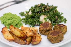 Ofenkartoffeln, Falafels, Erbsenmousse und Salat auf weißem Teller foto