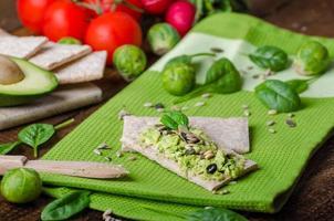 Home Avocado auf Knäckebrot mit Samen verteilt foto