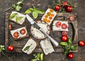 Scheibe frisches Roggenbrot mit Frischkäse-Basilikum-Tomaten foto