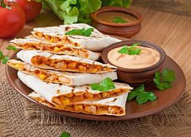 mexikanische Quesadilla in Scheiben geschnitten mit Gemüse und Saucen foto