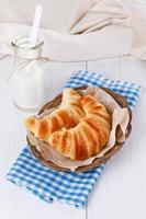 frisch gebackene Croissants auf gewebtem Teller über weißem Holzrücken foto