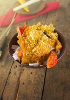 asiatisches Gericht mit Reisnudeln und Paprika auf altem Holz