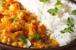Garnelen in Currysauce mit Reis und Koriander Makro horizontal foto