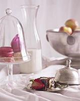 Makronen, Schokoladeneiskuchen, Äpfel und Milch foto
