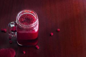 Rote-Bete-Smoothie gesund und Kraut auf Holztischhintergrund