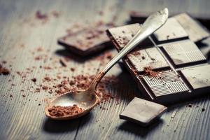 Nahaufnahme der Kakaokraft auf Löffel und dunklen Schokoladenquadraten foto