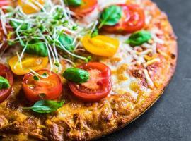 Pizza mit Tomaten und Basilikum foto