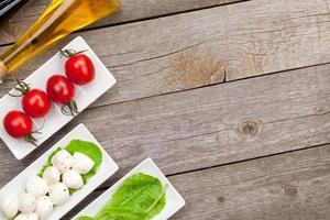 Tomaten, Mozzarella und grüne Salatblätter mit Gewürzen foto