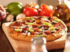 Höchste italienische Pizza mit Peperoni und Toppings foto