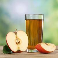 gesundes Apfelsaftgetränk und rote Äpfel im Herbst foto