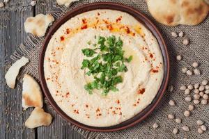 Schüssel Hummus, cremiges vegetarisches Essen mit Kichererbsen, Paprika foto